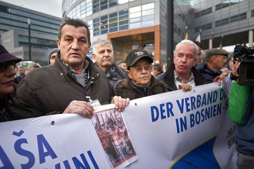 Fikret Alic, left, holds a banner outside the Yugoslav War Crimes Tribunal, ICTY, as he waits for the verdict to be handed down in the genocide trial against former Bosnian Serb military chief Ratko Mladic, in The Hague, Netherlands, Wednesday Nov. 22, 2017. Alic, a Bosnian man who became a figurehead for the suffering of Bosnians during the war when he was photographed as an emaciated prisoner behind the wire of a Bosnian Serb prison camp, was among those waiting to watch the hearing.