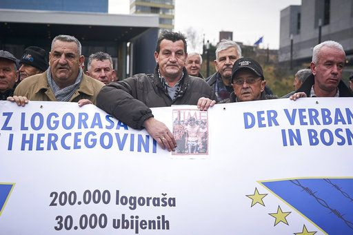 Fikret Alic, center, holds a banner outside the Yugoslav War Crimes Tribunal, ICTY, as he waits for the verdict to be handed down in the genocide trial against former Bosnian Serb military chief Ratko Mladic, in The Hague, Netherlands, Wednesday Nov. 22, 2017. Alic, a Bosnian man who became a figurehead for the suffering of Bosnians during the war when he was photographed as an emaciated prisoner behind the wire of a Bosnian Serb prison camp, was among those waiting to watch the hearing.