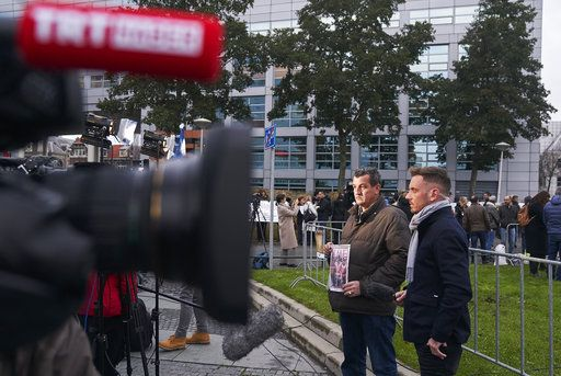 Fikret Alic, left, holds holds a copy of a magazine bearing his image, outside the Yugoslav War Crimes Tribunal, ICTY, as he waits for the verdict to be handed down in the genocide trial against former Bosnian Serb military chief Ratko Mladic, in The Hague, Netherlands, Wednesday Nov. 22, 2017. Alic, a Bosnian man who became a figurehead for the suffering of Bosnians during the war when he was photographed as an emaciated prisoner behind the wire of a Bosnian Serb prison camp, was among those waiting to watch the hearing.