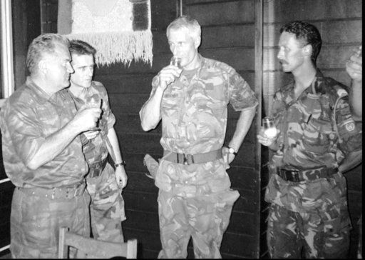 FILE - In this July 12, 1995 photo, Bosnian Serb army Commander General Ratko Mladic, left, drinks toast with Dutch U.N Commander Tom Karremans, second right, while others unidentified look on in village of Potocari, some 5 kilometers (3 miles) north of Srebrenica. Ratko Mladic will learn his fate on Nov. 22, 2017, when U.N. judges deliver verdicts in his genocide and war crimes trial.