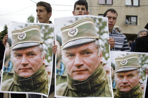 FILE - A May 29, 2011 file photo shows Bosnian Serb protesters holding posters depicting former Bosnian Serb army chief Ratko Mladic, during a protest in Mladic's hometown of Kalinovik, Bosnia-Herzegovina. Ratko Mladic will learn his fate on Nov. 22, 2017, when U.N. judges deliver verdicts in his genocide and war crimes trial.