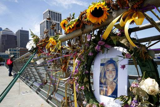 FILE - In this July 17, 2015 file photo, flowers and a portrait of Kate Steinle remain at a memorial site on Pier 14 in San Francisco. Attorneys were beginning their final arguments Monday, Nov. 20, 2017, in the trial of Zarate, accused of killing a woman on a San Francisco pier in a case that touched off a national immigration debate. The trial resumed Monday morning with instructions to the jury reminding them not to read newspapers or view social media while they are considering the case. (Paul Chinn /San Francisco Chronicle via AP, File)
