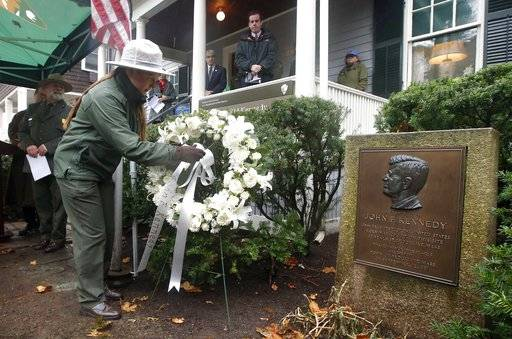 A National Park Ranger places a wreath outside John F. Kennedy's childhood home in Brookline, Mass., Wednesday, Nov. 22, 2017, on the 54th anniversary of Kennedy's assassination in Dallas in 1963. (AP Photo/Michael Dwyer)