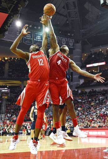 Houston Rockets forward PJ Tucker (4) and forward Luc Mbah a Moute (12) reach for a rebound during the first half of an NBA basketball game against the Denver Nuggets, Wednesday, Nov. 22, 2017, in Houston. (AP Photo/Eric Christian Smith)