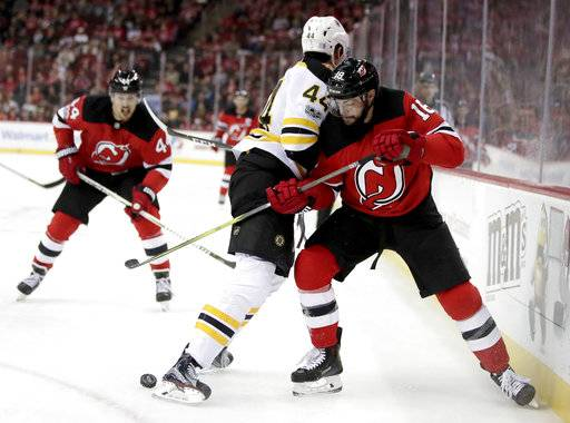 Boston Bruins defenseman Rob O'Gara (44) and New Jersey Devils right wing Drew Stafford (18) compete for the puck during the second period of an NHL hockey game, Wednesday, Nov. 22, 2017, in Newark, N.J. (AP Photo/Julio Cortez)