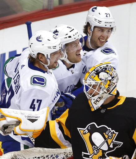 Vancouver Canucks' Brock Boeser (6) celebrates his goal with Sven Baertschi (47) and Ben Hutton (27) behind Pittsburgh Penguins goalie Matt Murray (30) during the first period of an NHL hockey game in Pittsburgh, Wednesday, Nov. 22, 2017. (AP Photo/Gene J. Puskar)