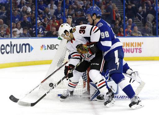 Tampa Bay Lightning defenseman Mikhail Sergachev (98) moves Chicago Blackhawks left wing Ryan Hartman (38) from in front of goalie Andrei Vasilevskiy (88) during the first period of an NHL hockey game Wednesday, Nov. 22, 2017, in Tampa, Fla. (AP Photo/Chris O'Meara)