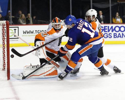 New York Islanders' Josh Bailey (12) shoots the puck past Philadelphia Flyers goalie Brian Elliott (37) for the game winning goal during the overtime period of an NHL hockey game Wednesday, Nov. 22, 2017, in New York. The Islanders won 4-3. (AP Photo/Frank Franklin II)
