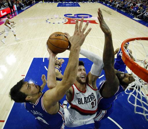 Portland Trail Blazers' Jusuf Nurkic, center, goes up for a shot between Philadelphia 76ers' Dario Saric, left, and Amir Johnson during the first half of an NBA basketball game, Wednesday, Nov. 22, 2017, in Philadelphia. (AP Photo/Matt Slocum)