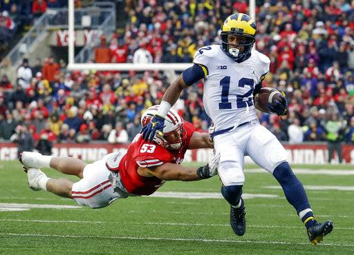 FILE - In this Nov. 18, 2017, file photo, Michigan's Chris Evans (12) runs past Wisconsin's T.J. Edwards, left, during the first half of an NCAA college football game in Madison, Wis. The unranked Wolverines need Evans to make all the right moves on the field at the Big House against No. 8 Ohio State. To pull off a big upset and spoil the Buckeyes' chances of playing for a national championship, Michigan might need Evans to have the kind of day Tshimanga Biakabutuka had in 1995 when he ran for 313 yards in one of the finest performances in the rivalry. (AP Photo/Morry Gash, File)