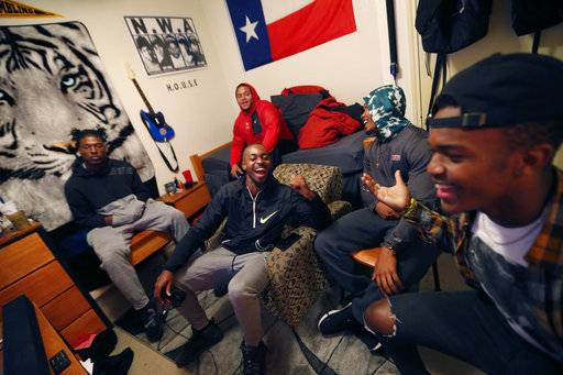In this Monday, Nov. 13, 2017 photo, Devante Kincade, center, quarterback for the Grambling's NCAA college football game college football team, laughs with friends while playing a video game in a dorm room at the university in Grambling, La. Kincade, who played two seasons at Mississippi , says playing football at a Historically Black College or University is an experience to savor. Playing at an HBCU is not just about entertaining halftime shows the schools are known for, it's about community. (AP Photo/Gerald Herbert)