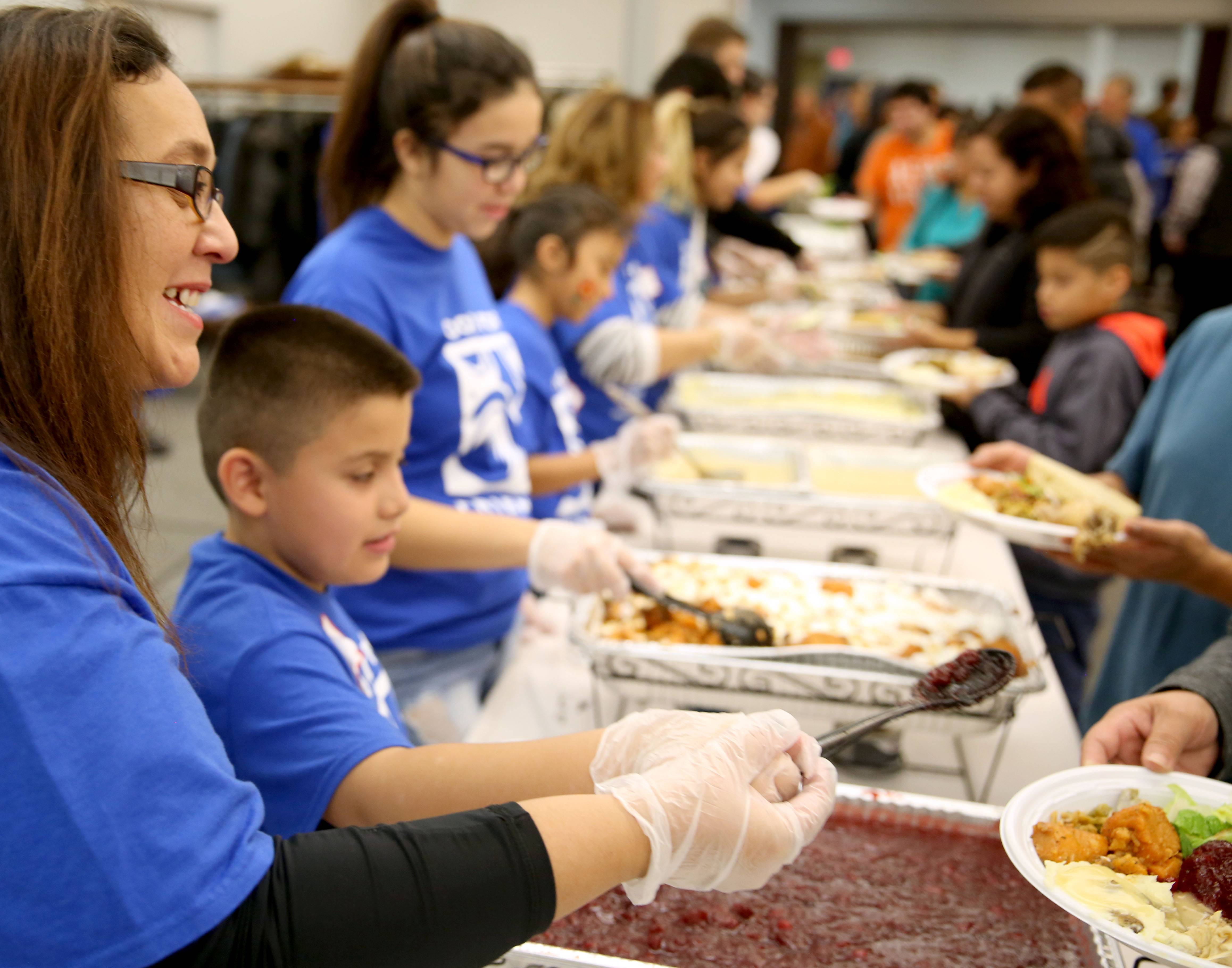 "Rocio Robledo of Elgin, left, offers a smile and a ""Happy Thanksgiving!"" as she dishes food with fellow volunteer Kevin Martinez, 8, of Geneva for the community Thanksgiving dinner at First United Methodist Church in Elgin on Thanksgiving Day. Robledo's daughters Victoria, 15, and Emma, 9, also volunteered and are working next to Kevin."