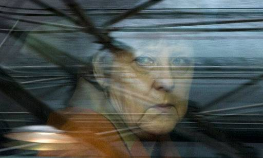 FILE - In this March 7, 2016 file photo, German Chancellor Angela Merkel looks out of her car window as she arrives for an EU summit at the EU Council building in Brussels. Germany, Europe's largest economy and anchor of stability, is facing the prospect of months of political uncertainty after Chancellor Angela Merkel's conservatives were unable to form a coalition with two smaller parties, raising the likelihood of new elections. (AP Photo/Virginia Mayo, File)