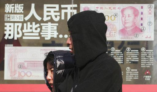 FILE - In this file photo taken Thursday, Nov. 24, 2016, residents walk past board highlighting the security markers on the latest Yuan note outside a bank in Beijing, China. Chinese police say they have broken up a gang that smuggled 20 billion yuan ($3 billion) out of the country, evading financial controls imposed by Beijing to stem an outflow of capital from the economy.(AP Photo/Ng Han Guan, File)