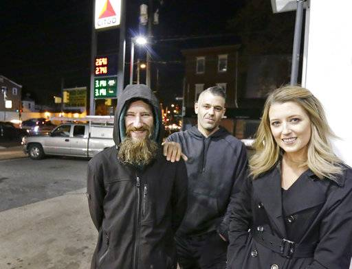 FILE- In this Nov. 17, 2017, photo, Johnny Bobbitt Jr., left, Kate McClure, right, and McClure's boyfriend Mark D'Amico pose at a Citgo station in Philadelphia. When McClure ran out of gas, Bobbitt, who is homeless, gave his last $20 to buy gas for her. McClure started a Gofundme.com campaign for Bobbitt that has raised more than $275,000. (Elizabeth Robertson/The Philadelphia Inquirer via AP, File)