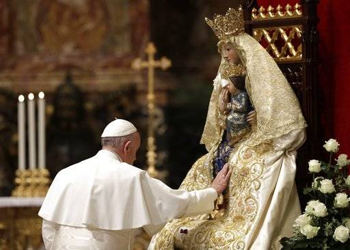 Pope Francis touches a statue of Mary and Jesus as he celebrates a prayer for peace in South Sudan and the Democratic Republic of Congo, inside St. Peter's Basilica, at the Vatican, Thursday, Nov. 23, 2017. (AP Photo/Gregorio Borgia)