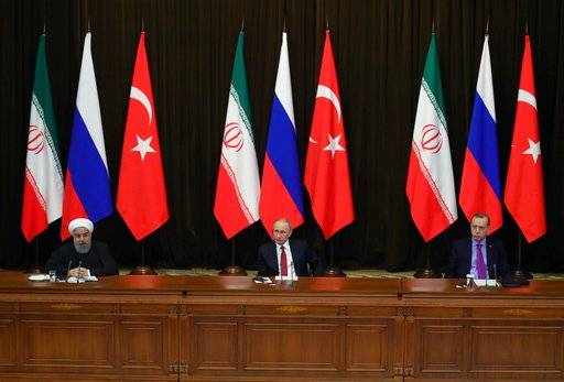 Turkey's President Recep Tayyip Erdogan, right, Russia's President Vladimir Putin, center, and Iran's President Hassan Rouhani attend a news conference in Russia's Black Sea resort of Sochi, Russia, Wednesday, Nov. 22, 2017. The presidents of Turkey and Iran have hailed their trilateral talks with Russia on Syria's future as critical for restoring peace in the war-torn nation. (Mikhail Klimentyev/Pool Photo via AP)