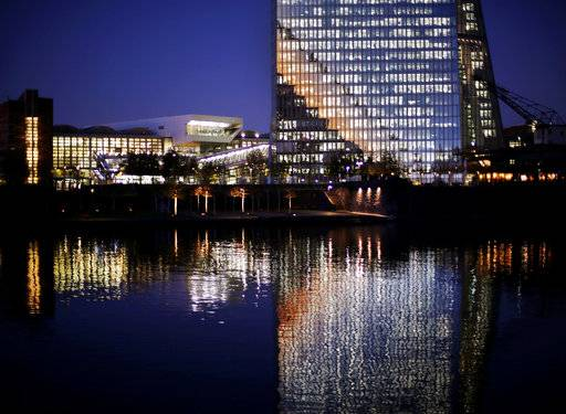 The bottom part of the European Central Bank is reflected in the Main river in Frankfurt, Germany, Wednesday, Nov. 22, 2017. (AP Photo/Michael Probst)