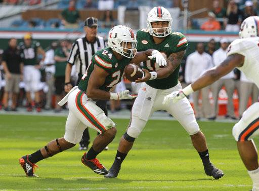 In this Saturday, Nov. 18, 2017 file photo, Miami quarterback Malik Rosier, right, hands off the football to running back Travis Homer (24) during the first half of an NCAA college football game against Virginia in Miami Gardens, Fla. Pittsburgh plays Miami on Friday, Nov. 24, 2017. (AP Photo/Lynne Sladky, File)