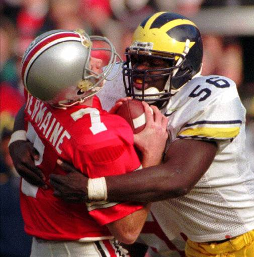 FILE - In this Nov. 23, 1996, file photo, Ohio State quarterback Joe Germaine, left, is sacked by Michigan defender James Hall, ending a drive during the third quarter of an NCAA college football game in Michigan's 13-9 upset victory over No. 2 Ohio State at Ohio Stadium in Columbus, Ohio. (AP Photo/Charles Rex Arbogast, File)