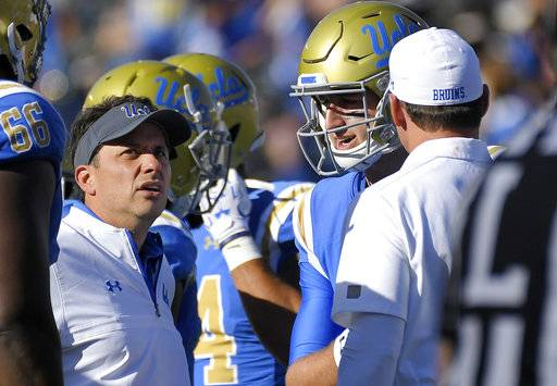 This photo taken Oct. 21, 2017, shows UCLA offensive coordinator Jedd Fisch, left, talking with quarterback Josh Rosen, center, and head coach Jim Mora during the second half of an NCAA college football game against Oregon in Pasadena, Calif. Fisch is UCLA's head coach for the week after Jim Mora's surprise firing, and he's hoping to extend that gig for at least another month. The veteran offensive coordinator has been promoted for the Bruins' season finale against California, and Fisch hopes to honor Mora's legacy with a win that would make UCLA bowl-eligible. (AP Photo/Mark J. Terrill)