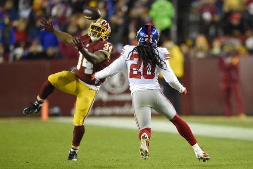 New York Giants cornerback Janoris Jenkins (20) scopes up a pass intended for Washington Redskins running back Byron Marshall (34) before returning the interception for a touchdown during the second half of an NFL football game in Landover, Md., Thursday, Nov. 23, 2017.
