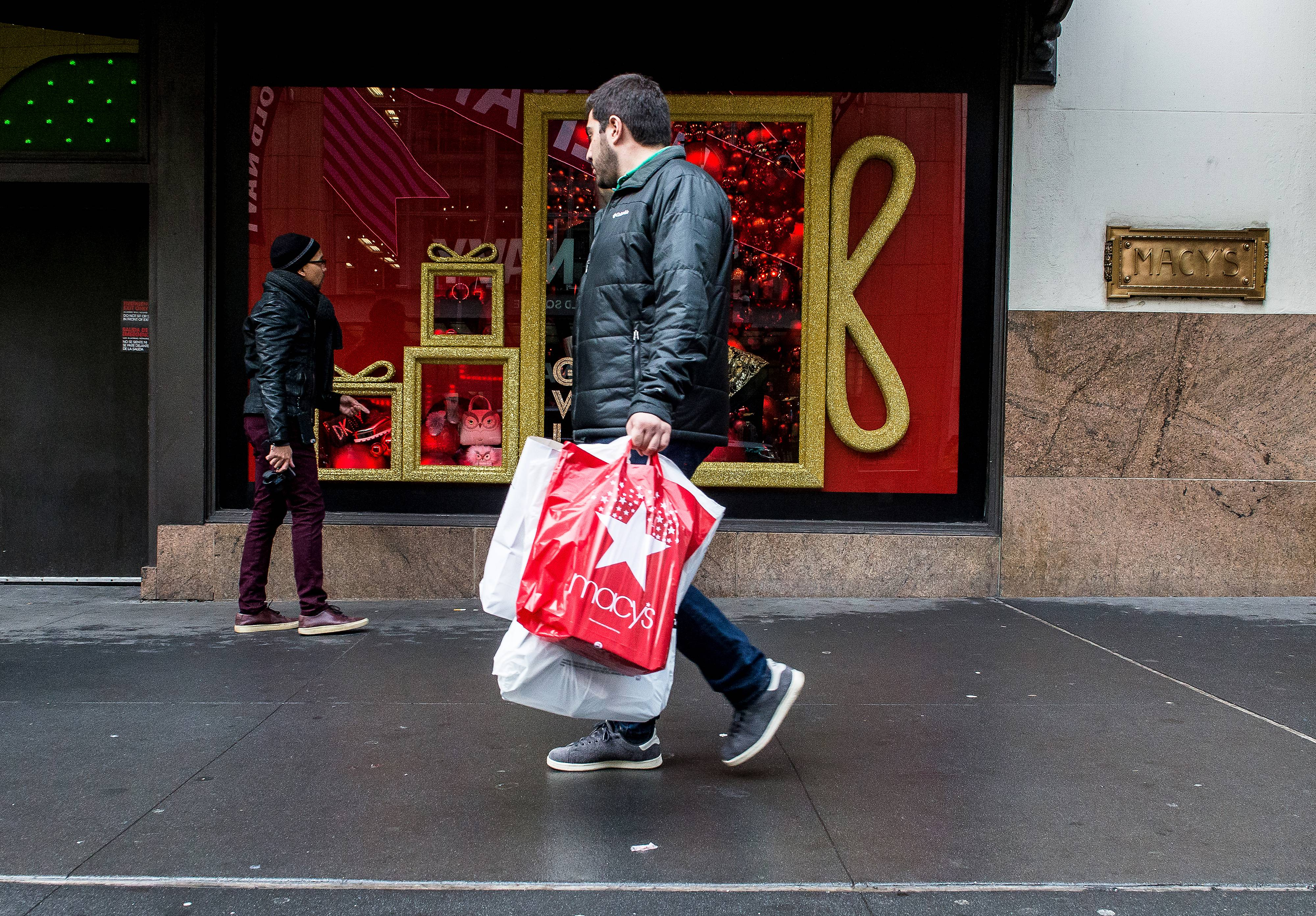 A pedestrian carries a Macy's Inc. shopping bag while walking past a store in New York in November.