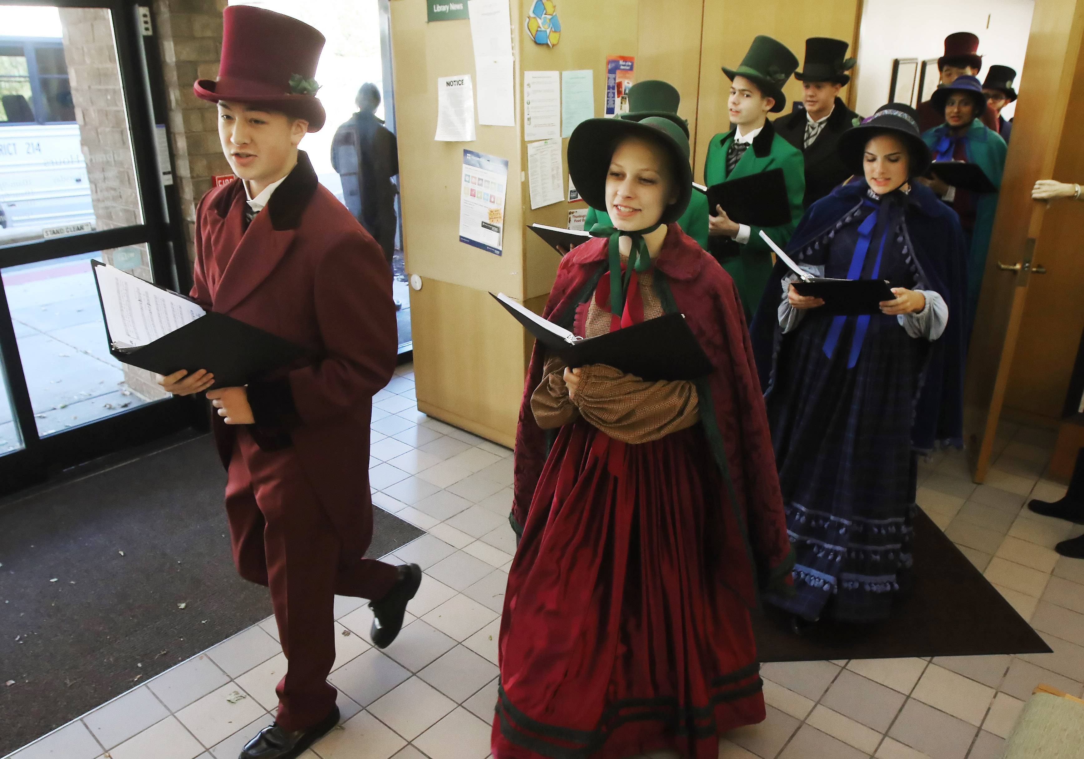 "Nathan Van Gelderen, left, and Isabelle Markworth lead the John Hersey High School Charles Dickens Carolers as they perform at the Prospect Heights Library on Sunday. The annual musical event featured 20 performers singing songs such as ""Jingle Bells"" and ""Joy to the World."""