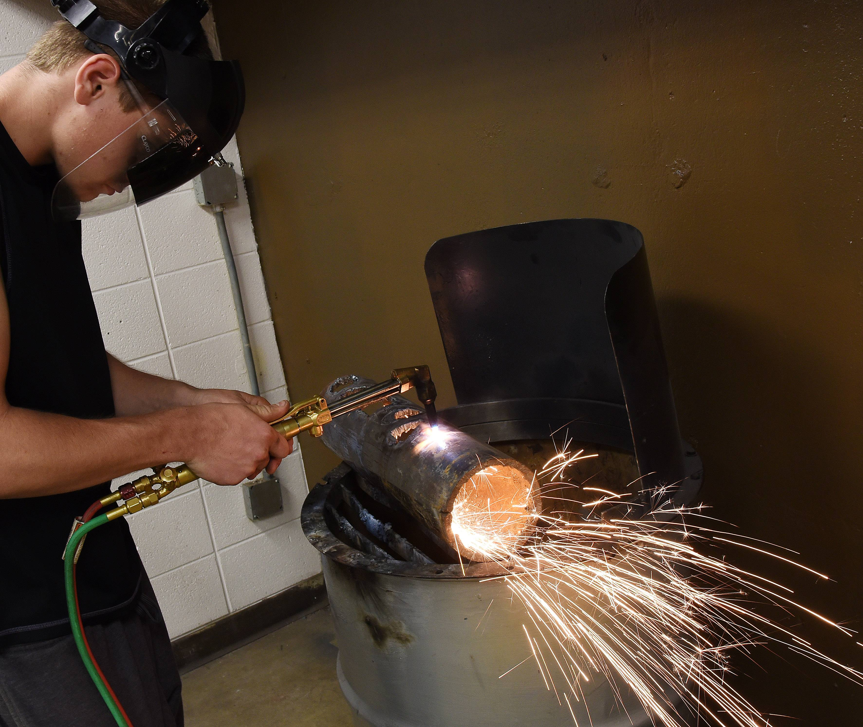 Senior J.J. Meyer uses an oxygen-acetylene cutting torch during a welding class at Elgin High School last spring. Elgin Area School District U-46 plans to spend $643,000 renovating the school's welding lab.