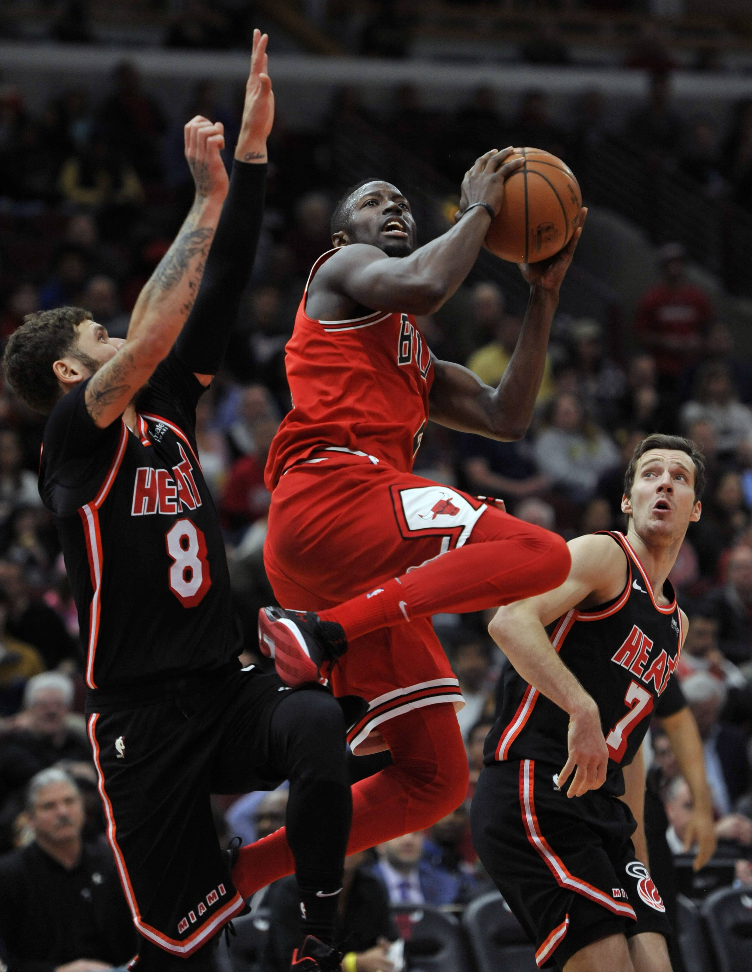 Chicago Bulls' Jerian Grant goes up for a shot against Miami Heat's Tyler Johnson (8) and Goran Dragic (7) of Slovenia, during the second half Sunday in Chicago. Miami won 100-93.