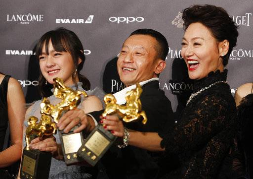 "Taiwanese actress Vicky Chen, from left, director Yang Ya Che and Hong Kong actress Kara Wai hold their awards for Best Supporting Actress, Best Feature Film and Best Leading Actress at the 54th Golden Horse Awards in Taipei, Taiwan, Saturday, Nov. 25, 2017. They won for the film "" The Bold, The Corrupt, and The Beautiful "" at this year's Golden Horse Awards -the Chinese-language film industry's biggest annual events.(AP Photo/ Chiang Ying-ying)"