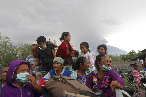Villagers sit on a truck during an evacuation following the eruption of Mount Agung, seen in the background, in Karangasem, Indonesia, Sunday, Nov. 26, 2017. The volcano on the Indonesian island of Bali has rumbled into life with a series of eruptions that temporarily disrupted some international flights to the popular tourist destination and dusted nearby resorts and villages with a thin layer of ash. (AP Photo/Firdia Lisnawati)