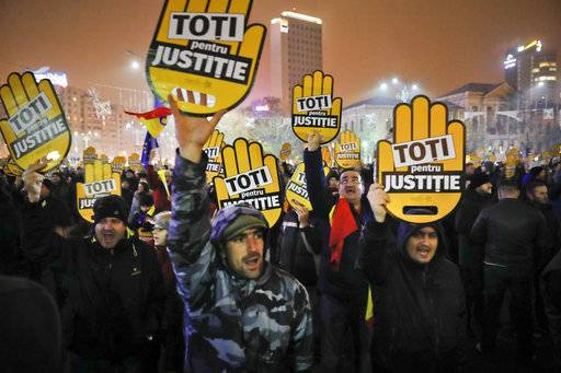 "People hold signs that read ""All for Justice"" during a protest outside the government headquarters in Bucharest, Romania, Sunday, Nov. 26, 2017. Thousands of Romanians have gathered in Bucharest and other cities to protest against government plans to introduce legislation they say will weaken efforts to root out corruption. (AP Photo/Vadim Ghirda)"