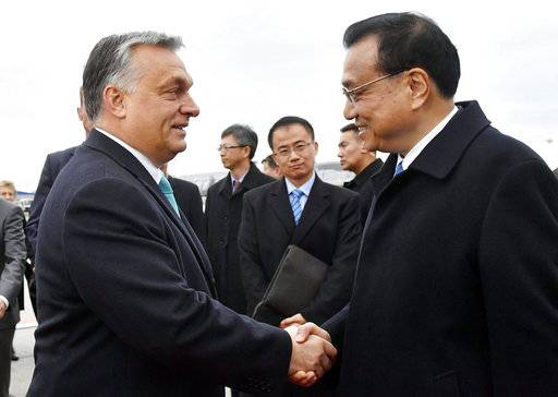 Hungarian Prime Minister Viktor Orban, left, welcomes Chinese Prime Minister Li Keqiang on the tarmac of Budapest Liszt Ferenc International Airport in Budapest, Hungary, Sunday, Nov. 26, 2017. The Chinese Premier arrived for the 6th Central Eastern European Countries and China (CEEC-China 16+1) Summit to be held the following day in Budapest. (Tibor Illyes/MTI via AP)