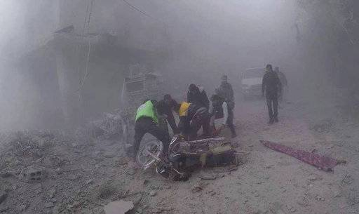 In this photo provided by the Syrian Civil Defense group in Damascus suburbs known as the White Helmets, Civil Defense workers carry an injured man after government airstrikes hit Douma, near Damascus, Syria, Sunday Nov. 26, 2017. Government airstrikes and shelling outside the Syrian capital killed at least 22 civilians, activists reported Sunday, as the fighting showed no signs of letting up ahead of the resumption of U.N. peace talks in Geneva. (Syrian Civil Defense in Damascus suburbs via AP)