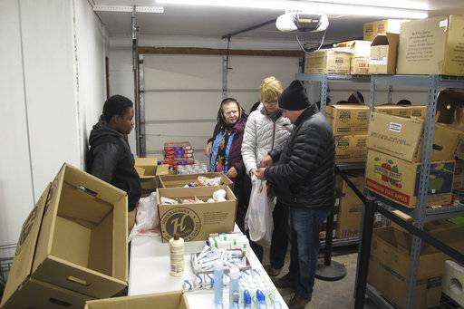 In this Nov. 16, 2017 photo, Legacy Children's Foundation executive director Mary Jean Dehne, center, and Legacy student Joel Gama, left, help people pick out groceries at the foundation's food panty in Fargo, N.D. The foundation is an after-school program meant to help students graduate from high school and help in the community. The student-run pantry provided 1,500 pounds of groceries in its first two weeks of operation. (AP Photo/Dave Kolpack)