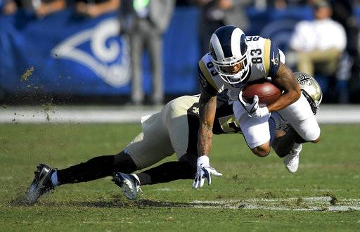 Los Angeles Rams wide receiver Josh Reynolds is tackled by New Orleans Saints cornerback De'Vante Harris during the first half of an NFL football game Sunday, Nov. 26, 2017, in Los Angeles. (AP Photo/Mark J. Terrill)