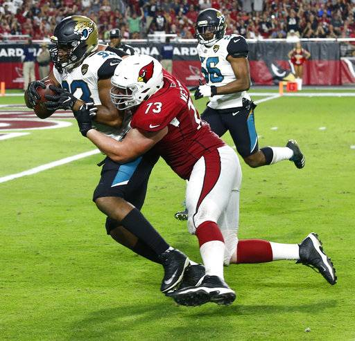Jacksonville Jaguars defensive end Calais Campbell (93) runs in a fumble recovery for a touchdown as Arizona Cardinals offensive tackle John Wetzel (73) defends during the second half of an NFL football game, Sunday, Nov. 26, 2017, in Glendale, Ariz. (AP Photo/Ross D. Franklin)