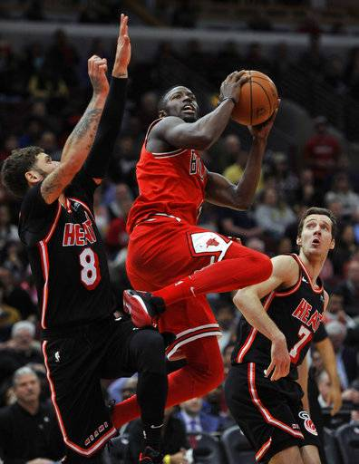Chicago Bulls' Jerian Grant (2) goes up for a shot against Miami Heat's Tyler Johnson (8) and Goran Dragic (7) of Slovenia, during the second half of an NBA basketball game, Sunday, Nov. 26, 2017, in Chicago. Miami won 100-93. (AP Photo/Paul Beaty)