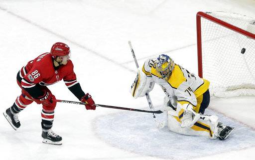 Carolina Hurricanes' Teuvo Teravainen (86), of Finland, scores against Nashville Predators goalie Juuse Saros (74), also of Finland, during a shootout in an NHL hockey game in Raleigh, N.C., Sunday, Nov. 26, 2017. (AP Photo/Gerry Broome)
