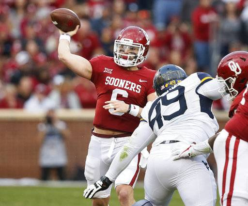 Oklahoma quarterback Baker Mayfield (6) passes under pressure from West Virginia West Virginia defensive lineman Lamonte McDougle (49) in the second quarter of an NCAA college football game in Norman, Okla., Saturday, Nov. 25, 2017. (AP Photo/Sue Ogrocki)