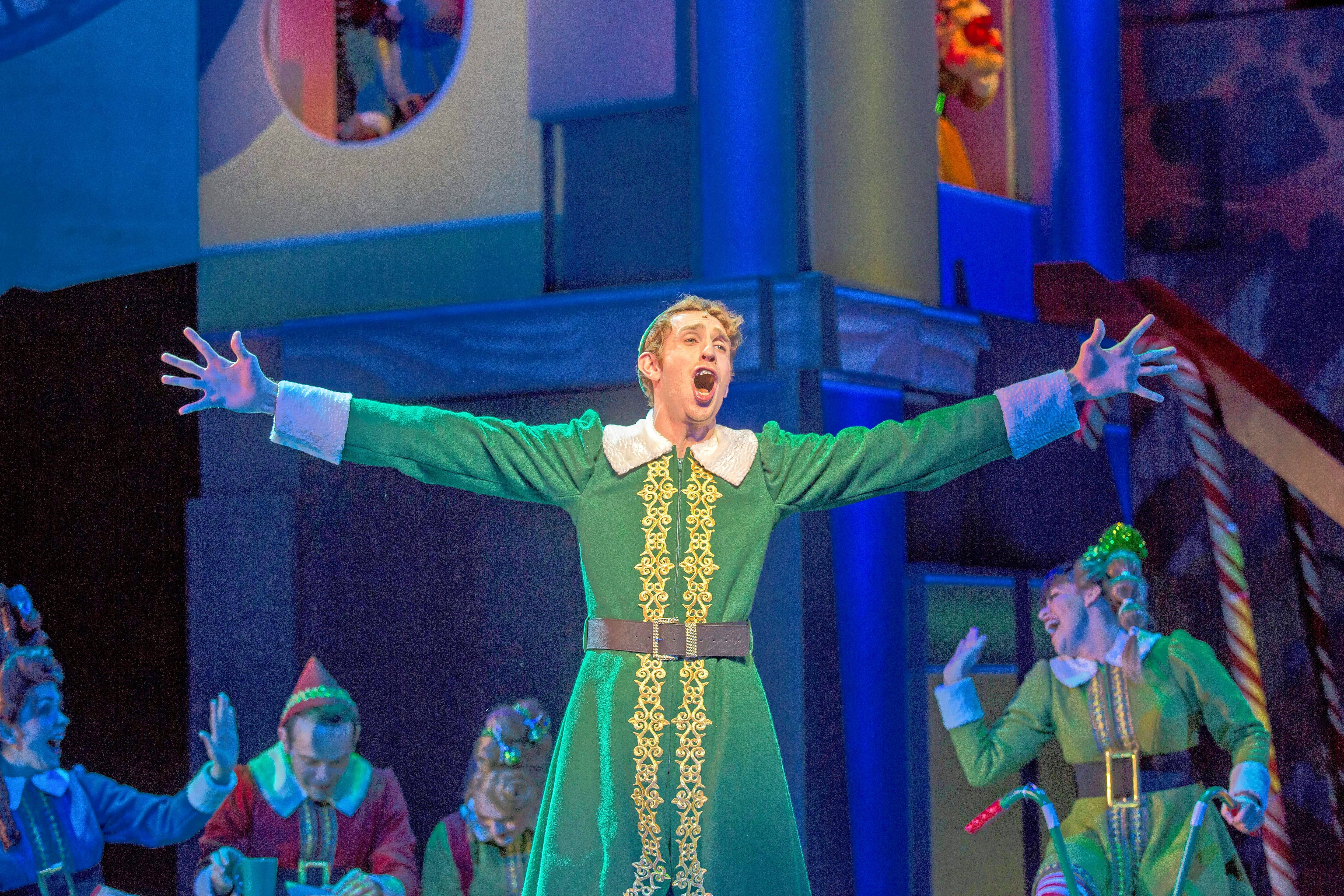 "Buddy the elf (Kyle Adams) sings about the wonders of ""Christmastown"" in ""Elf the Musical"" at the Paramount Theatre in Aurora."