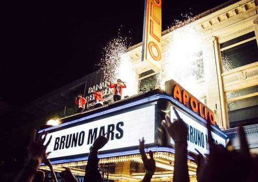 "Bruno Mars, center, during the taping of his TV special, ""BRUNO MARS: 24K MAGIC LIVE AT THE APOLLO,"" on top of the Apollo Theater marquee in New York. The special will air Nov. 29 on CBS."