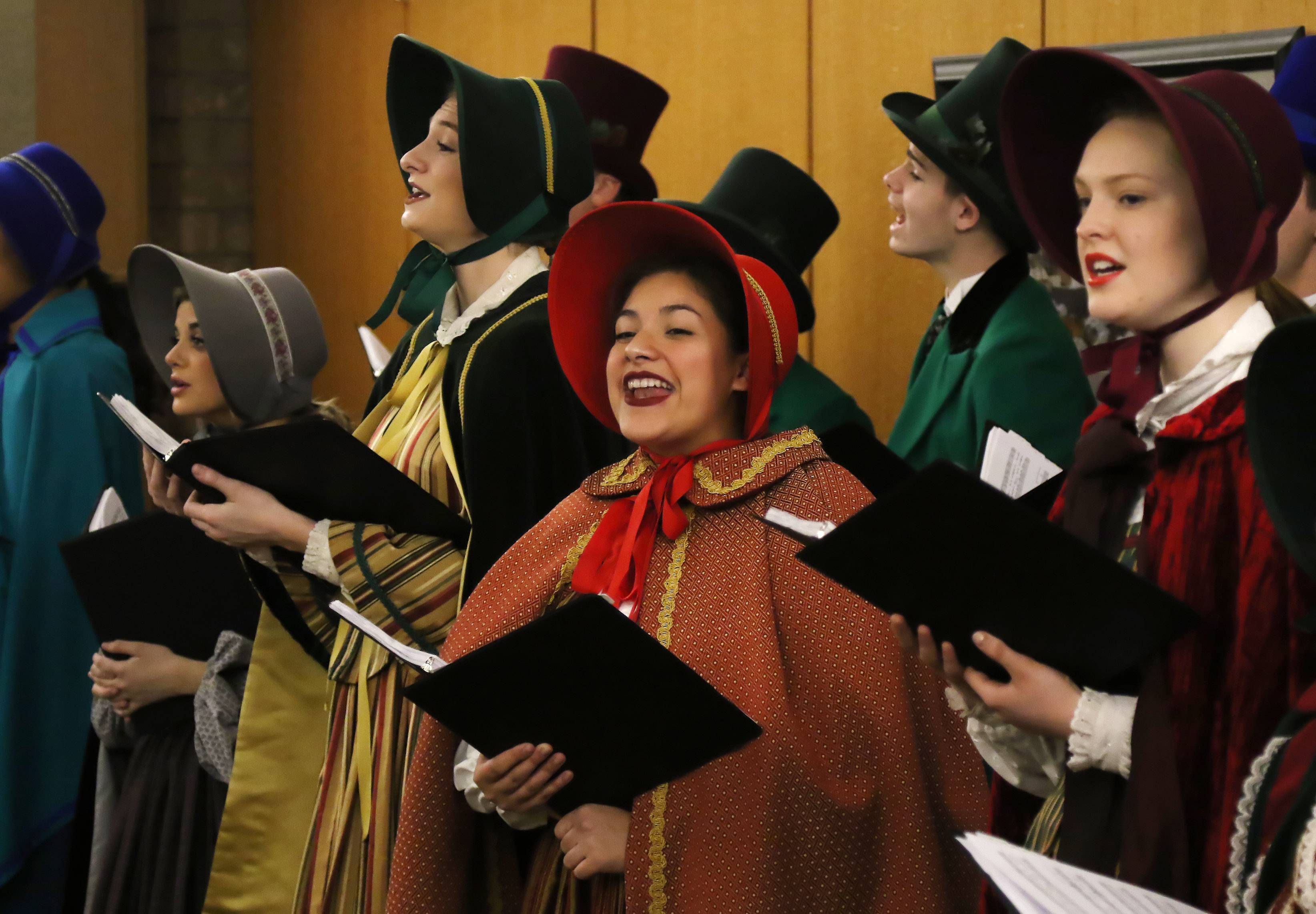 "Olivia Cano, in red, and Maggie Muglia, in yellow, sing with the John Hersey High School Charles Dickens Carolers as they performed at the Prospect Heights Library on Sunday. The annual musical event featured 20 performers singing songs such as ""Jingle Bells"" and ""Joy to the World."""