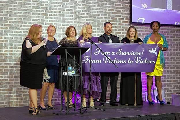 The Faces of Survival presentation highlighted the prevalence of domestic violence regardless of gender, race, income or circumstance. Narrator Kate Colbert, left, is on stage with survivors Connie Hanninen, Joyce Mason, Charlene Quint, Manny Hernandez, Julia Mason and Ozella Barnes.