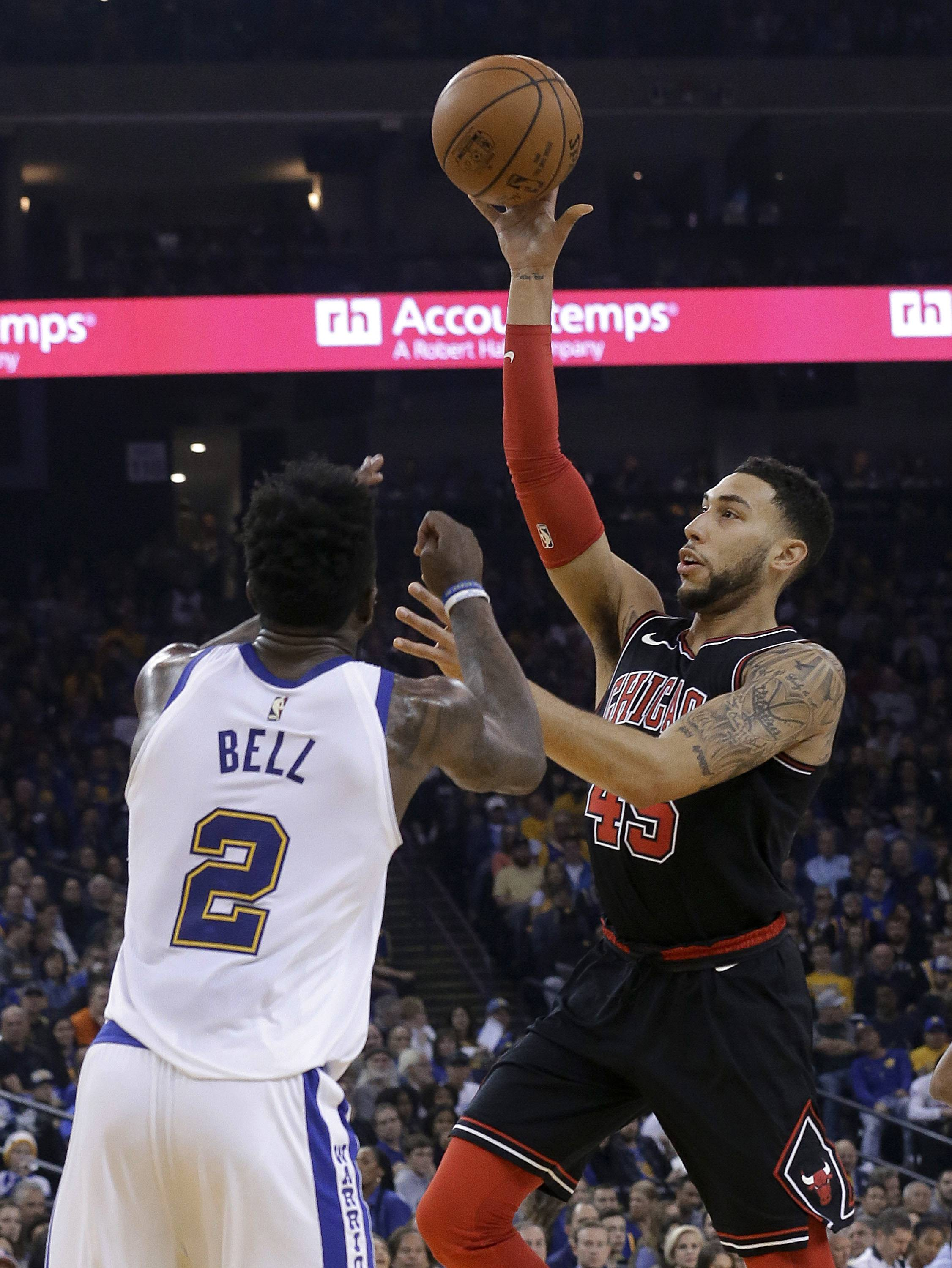 Chicago Bulls forward Denzel Valentine, right, shoots against Golden State Warriors forward Jordan Bell (2) during the first half of an NBA basketball game in Oakland, Calif., Friday, Nov. 24, 2017. (AP Photo/Jeff Chiu)