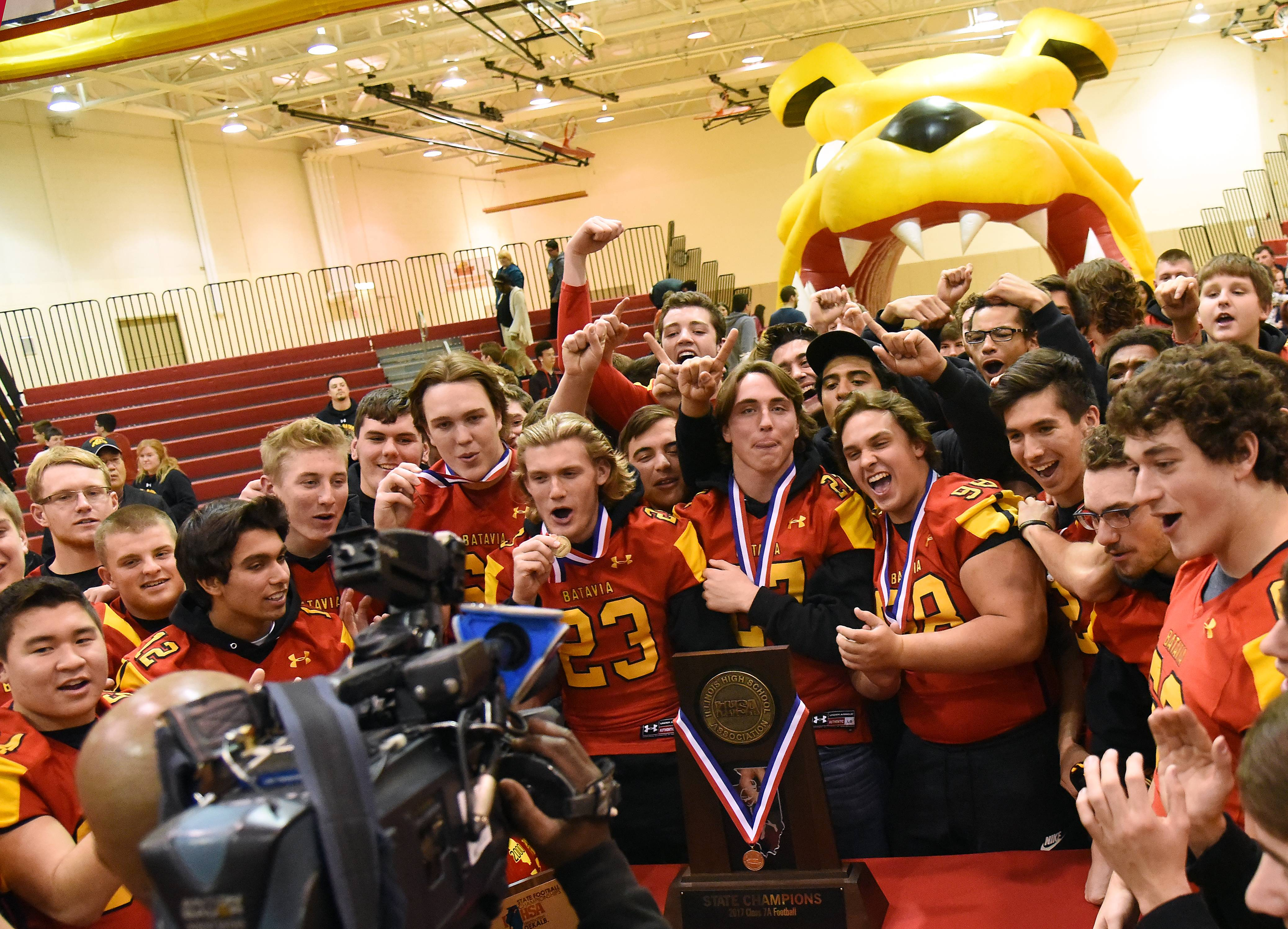 Batavia High School football players mug for a TV camera after an assembly at the school Monday to honor their state championship on Saturday in DeKalb. The Bulldogs defeated Lake Zurich 21-14 in overtime to win the IHSA Class 7A title.