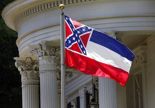 "FILE - In this June 23, 2015, file photo, the Mississippi state flag is unfurled against the front of the Governor's Mansion in Jackson, Miss. The U.S. Supreme Court on Monday, Nov. 27, 2017, rejected an appeal from African-American attorney Carlos Moore who called the Confederate battle emblem on the Mississippi flag ""an official endorsement of white supremacy."" The justices did not comment as they ended the lawsuit by Moore that sought to have the flag declared an unconstitutional relic of slavery. (AP Photo/Rogelio V. Solis, File)"