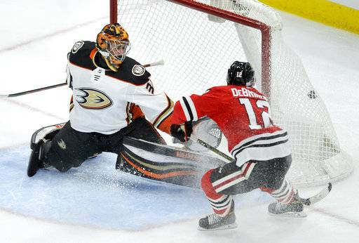 Chicago Blackhawks' Alex DeBrincat (12) scores a goal against Anaheim Ducks goalie John Gibson during the second period of an NHL hockey game, Monday, Nov. 27, 2017, in Chicago. (AP Photo/Paul Beaty)
