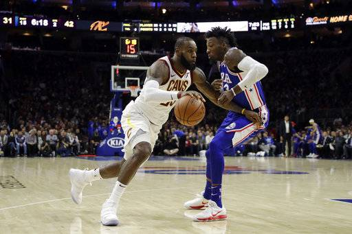 Cleveland Cavaliers' LeBron James, left, dribbles past Philadelphia 76ers' Robert Covington during the first half of an NBA basketball game, Monday, Nov. 27, 2017, in Philadelphia. (AP Photo/Matt Slocum)